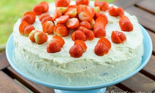 Jordgubbs- och marängtårta med marängbottnar smaksatta med kokos varvade med jordgubbssylt och garnerad med grädde och jordubbar.
