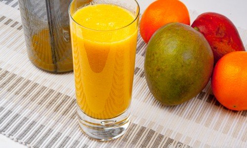 Ett glas juice med apelsin, mango och päron.