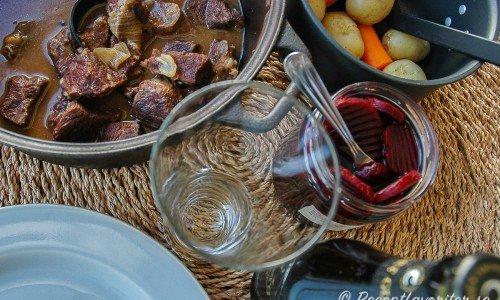 Kalops kokt i gjutjärnsgryta serverad med kokt potatis och morot samt inlagda rödbetor.