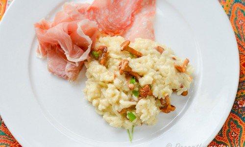 Risotto med kantareller serverade med lufttorkad italiensk skinka prosciutto samt salami.