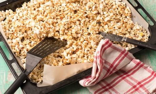 Blanda runt de varma popcornen med redskap. Varning - ta ej i den heta karamellen och servera ej innan popcornen svalnat riktigt
