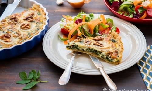 En bit kirskålspaj serverad med grönsallad på tallrik