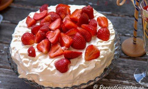 Klassisk midsommartårta med jordgubbar, tårtbottnar med vaniljkräm och grädde.