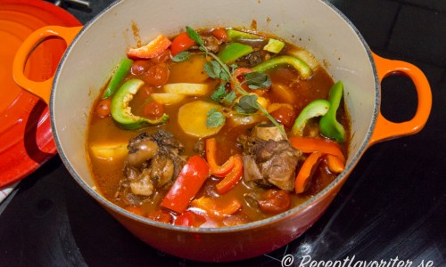 Lamm med ben kokas till gryta med potatis, tomater och grönsaker.