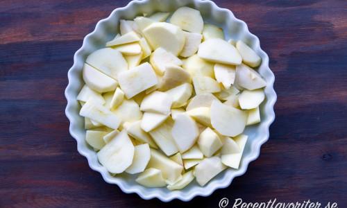 Skalade och urkärnade äpplen skurna i bitar i pajform till äppelpajen