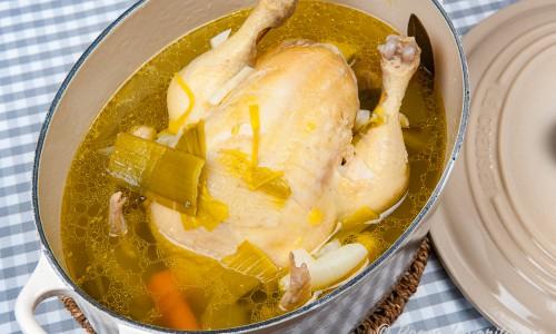 Kokt hel kyckling med buljong i gryta