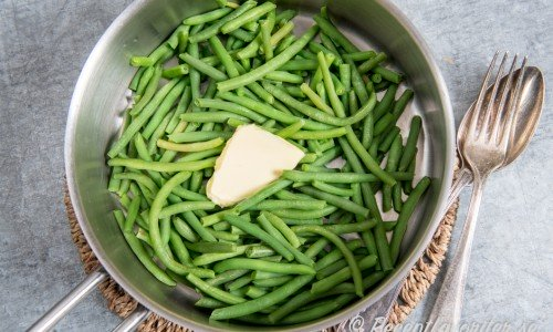 Kokta gröna bönor eller haricots verts är gott med en klick smör.