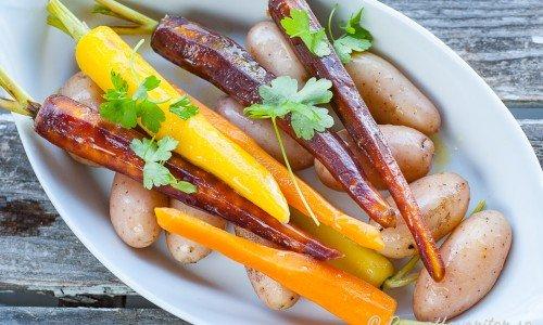 Kokta knippmorötter och delikatesspotatisar på fat garnerade med persilja