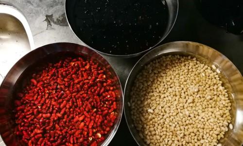Blötlagda svarta bönor, små vita bönor och adzukibönor i skålar.