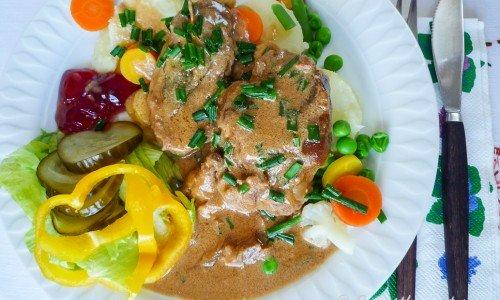 Kotletter i en gräddig sås med kokt potatis, grönsaker, inlagd gurka och sallad.