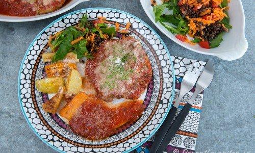 Kotletter med tomatsås och parmesan serverade med rostade rotfrukter och en god sallad med linser.