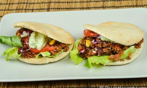 En variant på tacos med köttfärs i pitabröd istället för tortillabröd eller tacoskal - här med fräst köttfärs, guacamole, majs, rödlök, sallad, tomat och bönor.