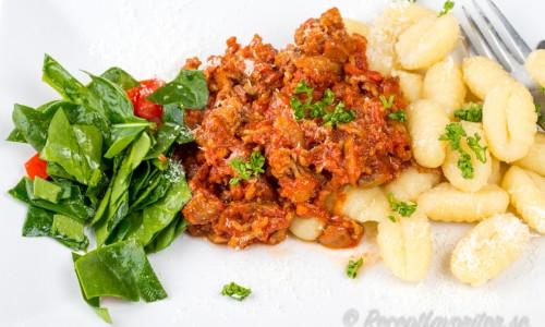 Köttfärssås med lammfärs - här med färsk gnocchi och spenat- och tomatsallad på tallrik.