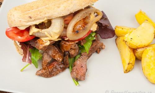 Köttmacka med stekt lök och Dijon i baguettebröd