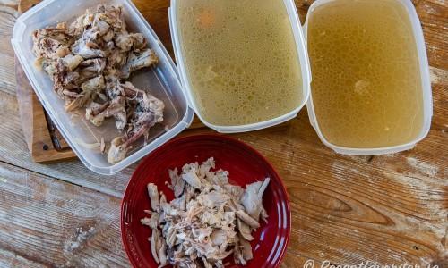 Två plastlådor med 3 liter buljong vardera samt kycklingkött plockat från skrov och ben i tallrik.