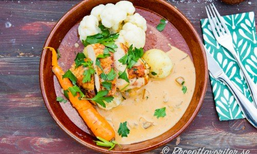 Stekt kycklingfilé med champinjonsås och grönsaker på tallrik
