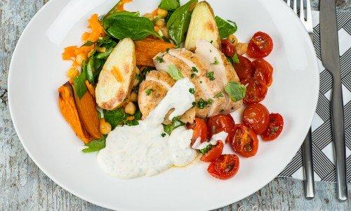 Kycklingfilé med tomater, kall bea-sås och rostad sötpotatis samt potatis på tallrik.