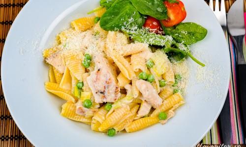 Kycklingfilé med pasta, parmesan och ärtor på tallrik med lite grönsallad