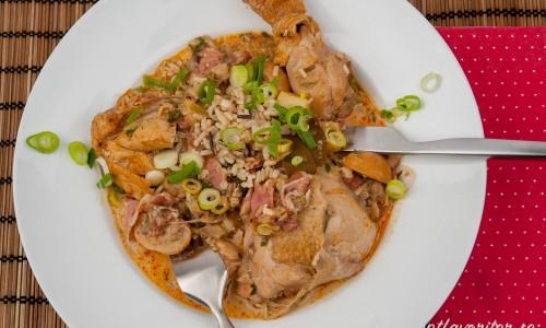 Kycklinggryta med bacon serverad med råris och strimlad salladslök som garnering.