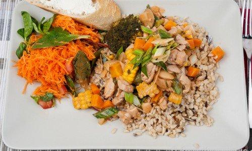 Kycklinggryta med bacon och grönsaker som broccoli, majs, purjolök, champinjoner, tomat med mera serverat med råris samt riven morot och mangoldskott. Nybakt baguette med färskost är gott till.