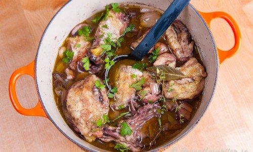 Kycklingen kokas med rött vin, lök, champinjoner och fläsk.