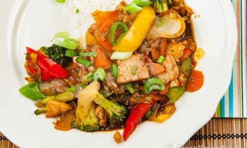 Kycklingwok med grönsaker på tallrik med ris