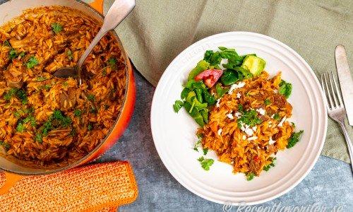 Mustig lammgryta med risoni serverad på tallrik med fetaost, parmesan, oregano och grönsallad.