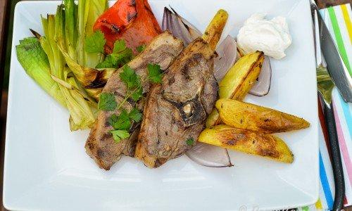 Grillade lammkotletter med grillade grönsaker, kall vitlökssås och rostad klyftpotatis med rödlök.