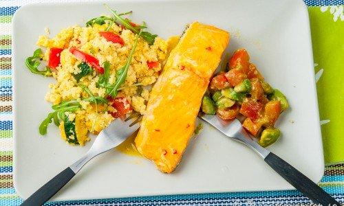 Grillad lax med citronglace och couscous och avokadosallad på tallrik