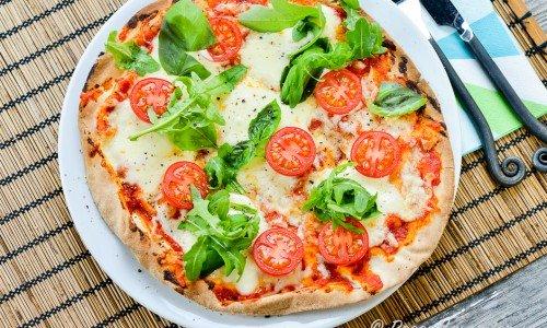 Libapizza med mozzarella, basilika, ruccola och tomat på tallrik