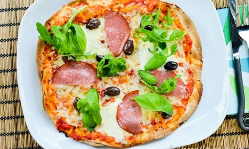 Libapizza med salami, mozzarella och oliver på tallrik