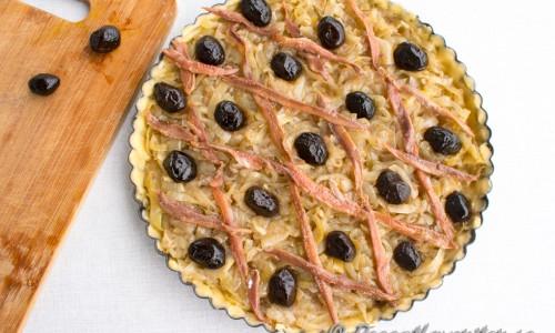 Kavla eller tryck ut pajdegen i en smörad pajform. Fyll med löken och lägg sedan sardeller och oliver i valfritt mönster. Klassiskt är ett rutmönster med sardeller och oliver i rutorna eller kryssen.