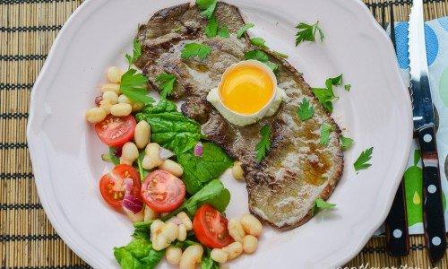Lövbiff med pepparrot, äggula och samt en sallad med vita bönor, tomat och babyspenat.