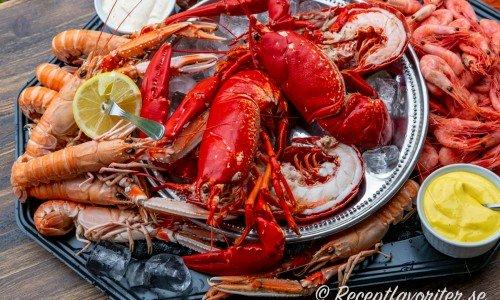 Lyxigt skaldjursfat med hummer, havskräftor och räkor samt såser.