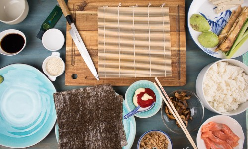 Lite olika grejer att fylla makirullar med: till höger tofu, avokado, gurka, tunn omelett, kokt sushiris, lätt stekt portabellosvamp i lite ljus soja, lax, rostad lök, majonnäs och srirachasås. Noriblad, sesamfrön och så ljus soja, wasabi och inlagd ingefära till servering.