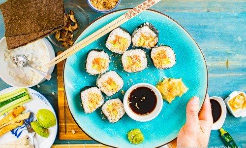Makirullar med lax, avokado och Srirachamajonnäs i bitar på tallrik