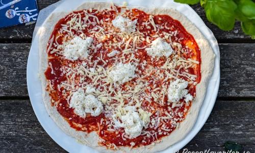 En Margherita pizza innan gräddning med tomatsås, riven mozzarella och färsk mozzarella.