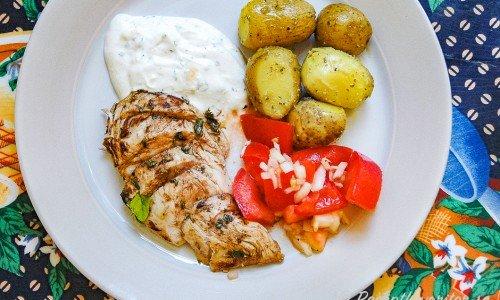 Marinerad kycklingfilé med örtyoghurtsås, fransk tomatsallad och pestopotatis på tallrik.