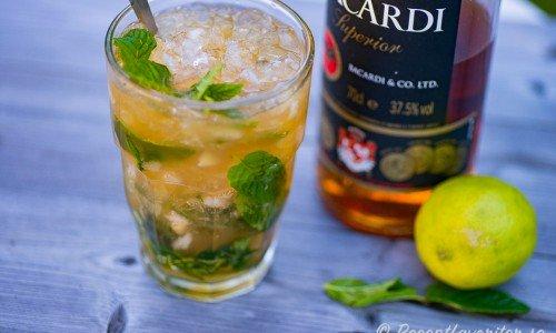 Mojito cocktail i glas med mynta, lime och rom