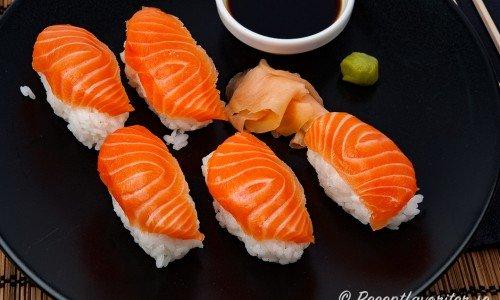 Nigiri sushi med lax, japansk soja, ingefära och grön pepparrot på tallrik.