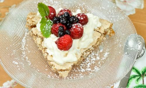 Nötmarängtårta med svenska hallon och blåbär samt garnerade med lite citronmeliss.