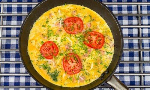 Omelett med skinka och tomat i panna
