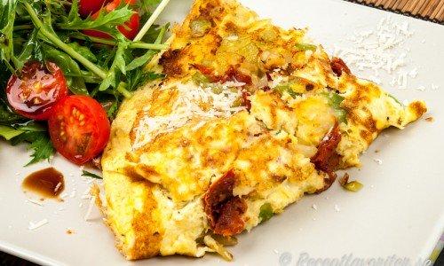 Omelett med soltorkade tomater på tallrik med sallad till