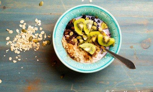 Overnight oats eller kallgröt - här med kiwi, blåbär, russin, pumpafrön, kanel och kall mjölk.