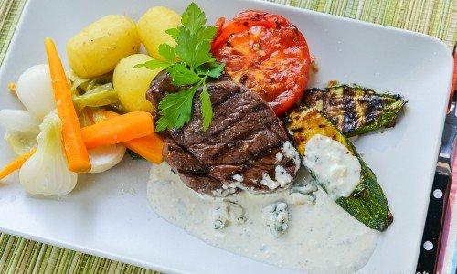 Grillad oxfilé med Gorgonzolasås, grillad skivad zucchini, grillad halv bifftomat, kokta knippmorötter och knipplök samt kokt färskpotatis.