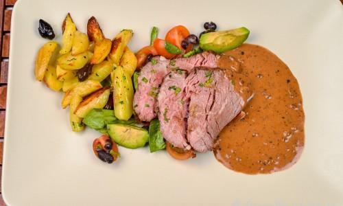 Oxfile med pepparsås, klyftpotatis med oliver och en grönsallad med avokado och tomat.