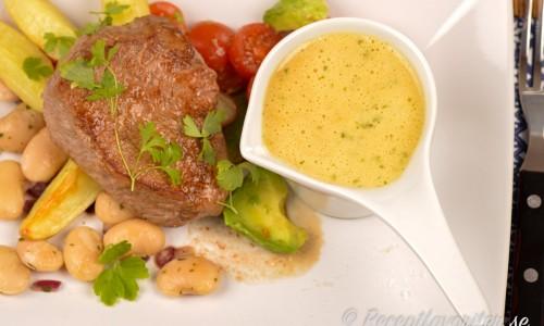 Sauce Colbert serverad med oxfilé, klyftpotatis samt en sallad med vita bönor, tomat och avokado.
