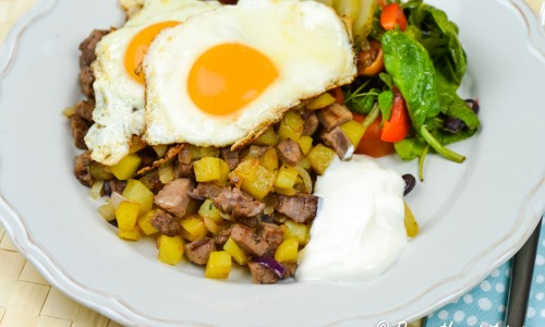 Pyttipanna med oxfilé, potatis och lök samt stekta ägg, crème fraiche och en grönsallad.