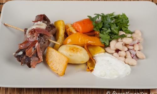 Serverade med rostad paprika, potatis, kålrot samt morot; sallad med vita bönor och ruccola samt en tzatziki.