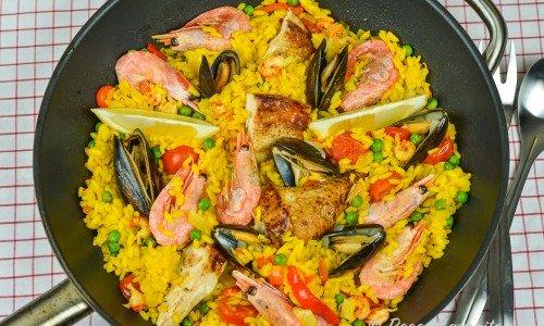 En panna paella med rundkornigt ris och saffran samt kyckling, musslor, räkor, ärtor och tomat.